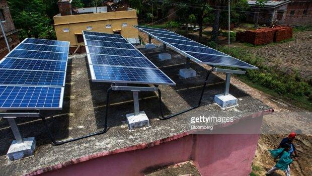 People Walk Past Solar Panels Mounted Roof