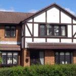 Tudor House White Brown Siding Brick Foundation